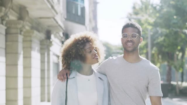 Young couple talking while walking in city