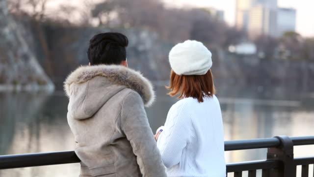vidéos et rushes de jeune couple parlant avec romance coucher de soleil sur le lac ensemble dans un parc public à osaka, japon - seulement des japonais