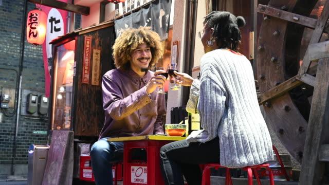 Young couple toast eachother at Tokyo Izakaya traditional inn Enjoying Japanese culture. Drinking outdoors clinking glasses at Tokyo Izakaya bar mixed race person stock videos & royalty-free footage