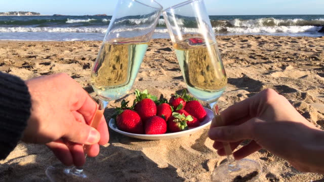 Young couple toasting on beach 4k video of young loving couple toasting with champagne and fresh strawberries on sandy beach. Mediterranean sea at the background. Relaxing video of travel, leisure and romance related vacation themes for vacations in the south France. Camera stabilization video, space for copy. aperitif stock videos & royalty-free footage