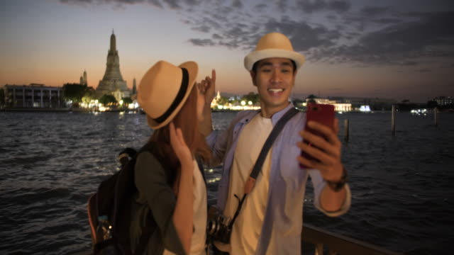 Young couple tourist taking selfies with mobile