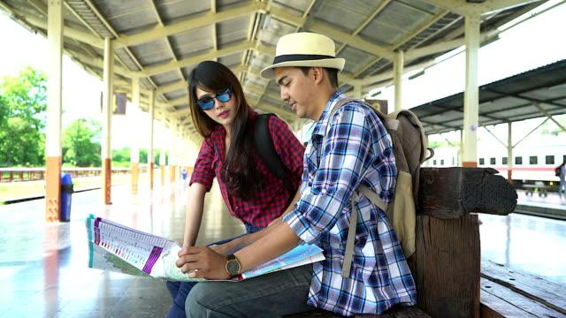 Joven pareja busca mapa viajero y discutir su viaje en la estación de tren. - vídeo