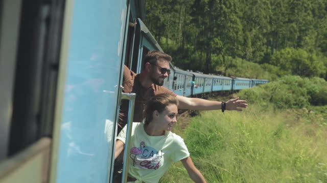 Young couple traveling on train Young crazy couple looking out of train sri lanka stock videos & royalty-free footage