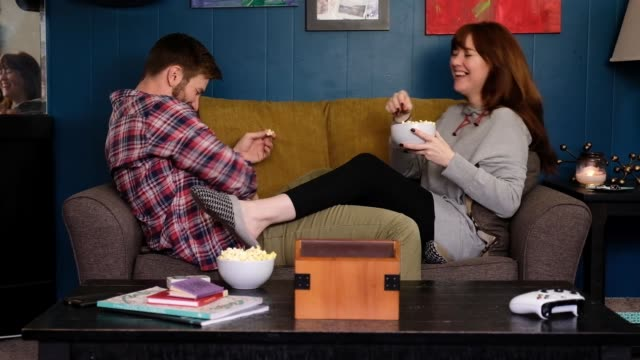 young couple try to catch popcorn in their mouth - date night stock videos & royalty-free footage