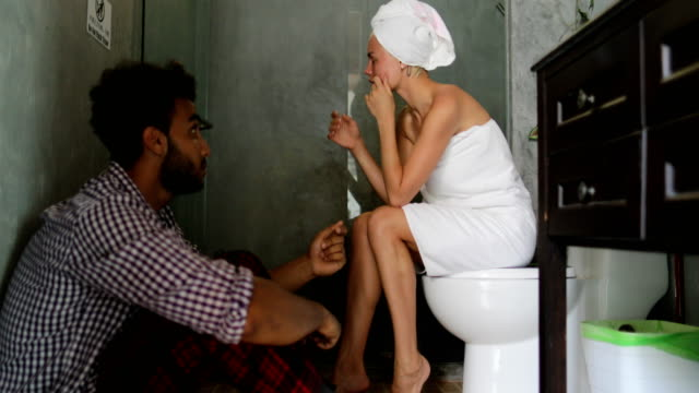 Young Couple Unhappy In Bathroom, Man And Woman Arguing Having Problem, Girl Crying Sitting On Toilet Guy On Floor video