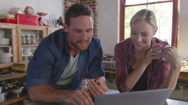 young couple using a laptop in kitchen, close up, front view, shot on r3d - financial planning stock videos and b-roll footage