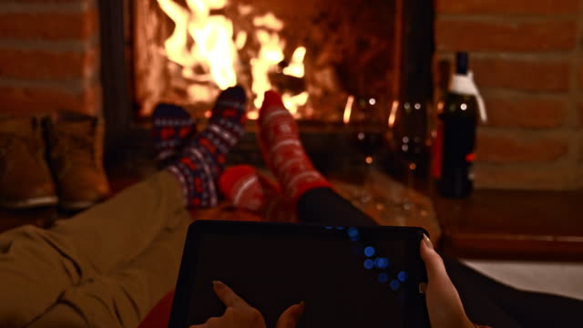 R/F Young couple using digital tablet by the fireplace video