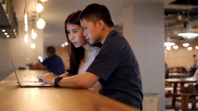 vidéos et rushes de jeune couple à l'aide de labtop ordinateur au bar - boisson chaude