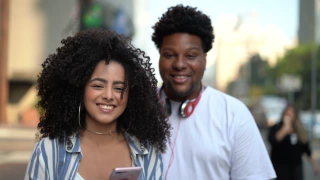 vídeos de stock, filmes e b-roll de jovem casal usando mobile ao ar livre - retrato - brasileiro pardo