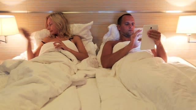 ungt par använder modern laptop, surfplatta liggandes på sängen på natten - bordsjordglob bildbanksvideor och videomaterial från bakom kulisserna