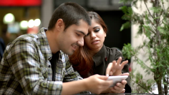 Young couple using smart phone video