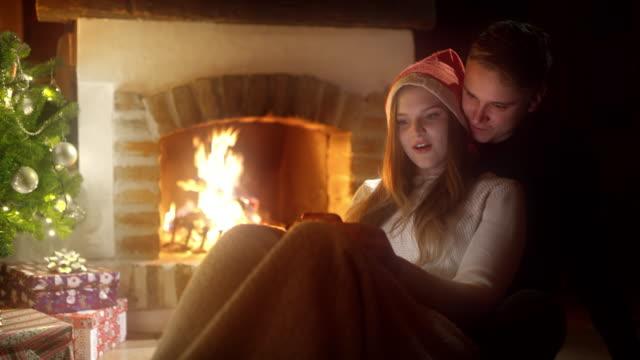 stockvideo's en b-roll-footage met ds young paar met behulp van smartphones bij de open haard op een kerstavond - christmas cabin