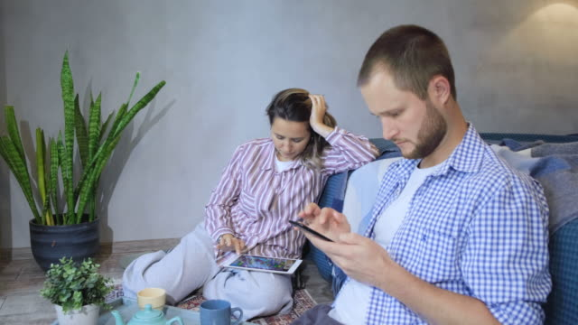 vídeos de stock e filmes b-roll de young couple using smartphones. cheerful young couple browsing smartphone and chatting pleasantly, successful marriage life - trabalho de design