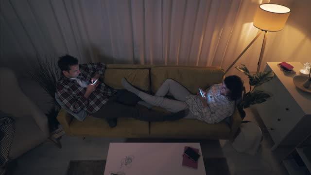 vídeos y material grabado en eventos de stock de pareja joven usando teléfonos inteligentes a altas horas de la noche. - acostado