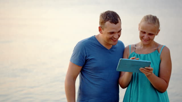 Young couple using tablet computer by the sea video
