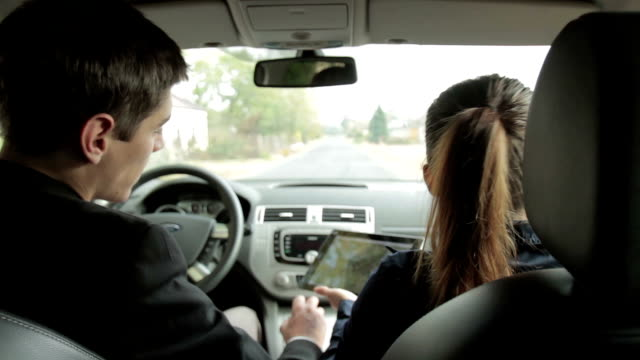 Young couple using tablet computer in a car, rear view video