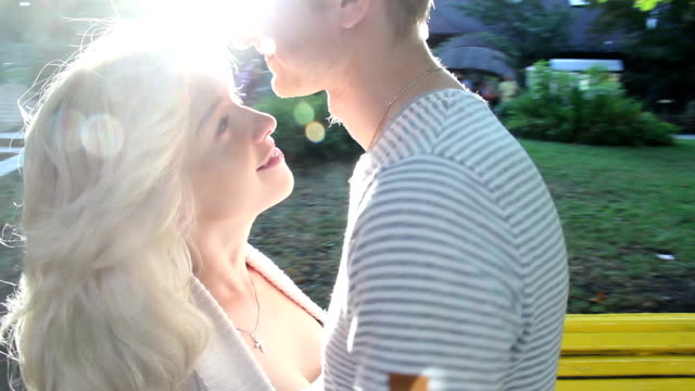 Young couple very romantic kissing in sun ray light park video