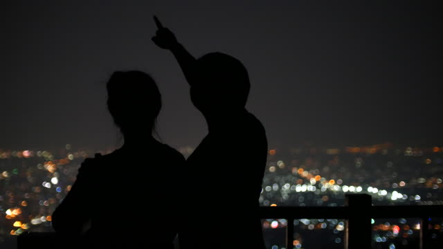 Young Couple viewing Stars on the background of the city at night urban scene, 4k(UHD) video