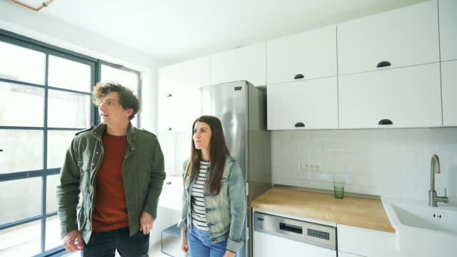 Young couple visiting a new house. Young couple visiting a new house. They are looking for a new home to buy or to rent. young couple stock videos & royalty-free footage