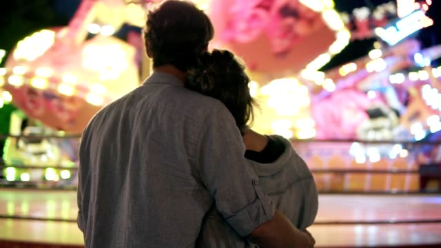young couple visiting an amusement park arcade together and hugging while standing next to a carousel ride with lights at night. standing from the back - date night stock videos & royalty-free footage