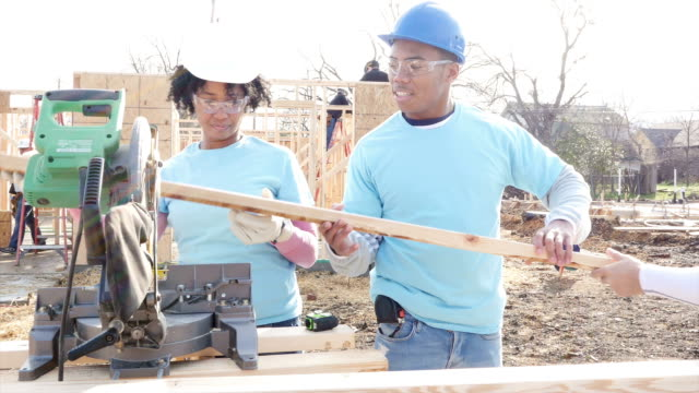 Young couple volunteers working together on home built for charity video