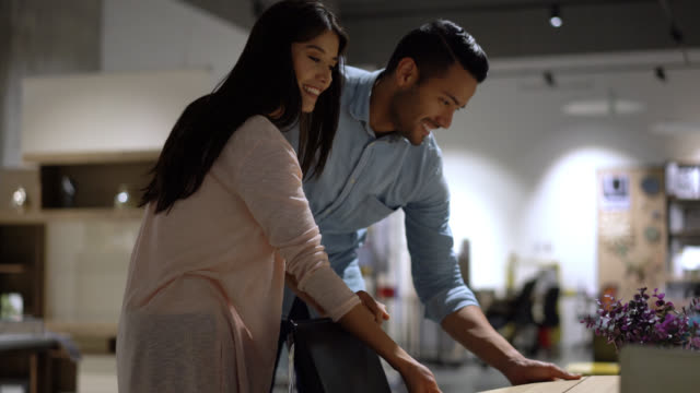 Young couple walking at a furniture store and looking at a table very happy