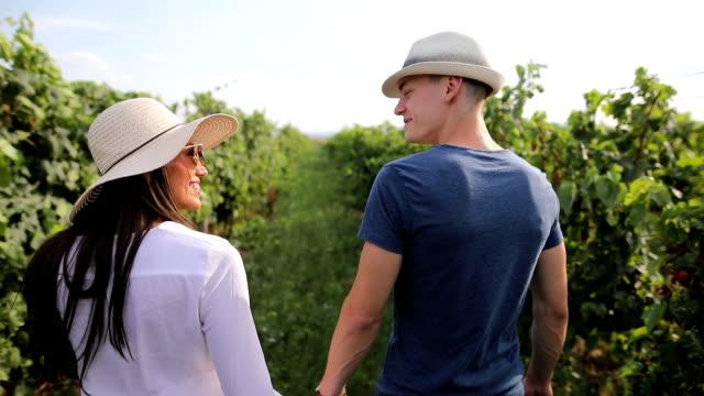 stockvideo's en b-roll-footage met jong paar weglopen, door prachtige wijngaard - flirten