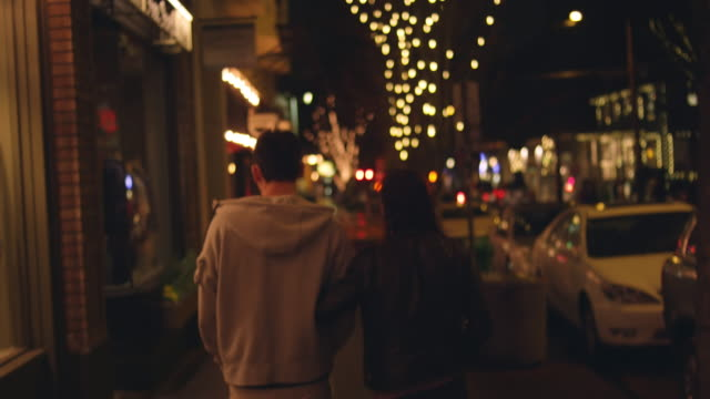 A young couple walking down a city sidewalk at night A young couple walking down a city sidewalk at night date night romance stock videos & royalty-free footage