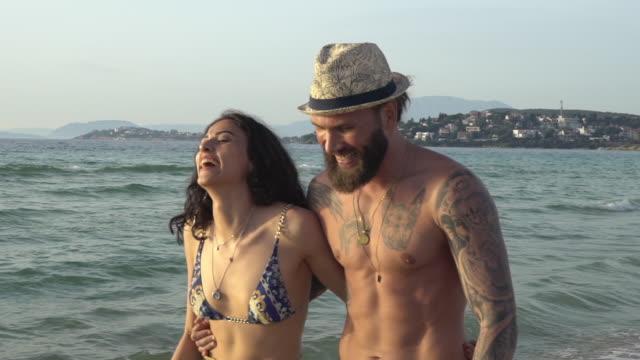 low-mo: junges paar spaziert am strand - nackter oberkörper stock-videos und b-roll-filmmaterial