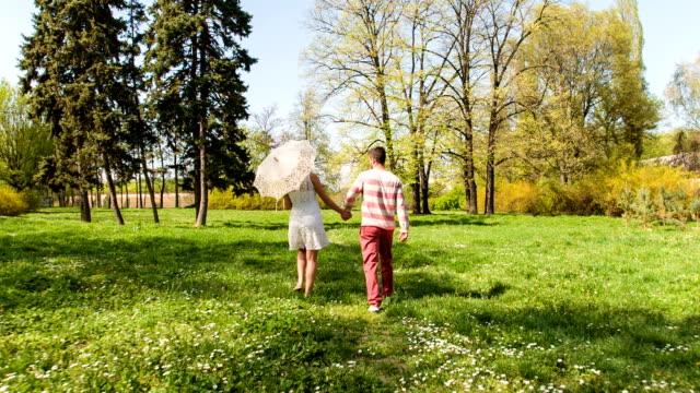 junge paar beim gehen durch den park im frühling - sonnenschirm stock-videos und b-roll-filmmaterial