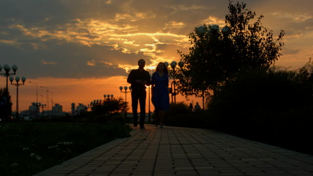 Young couple walking to the camera. Sunset video
