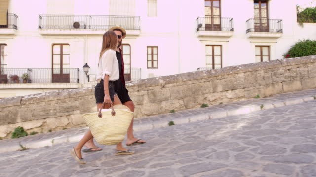 Young couple walking together on vacation in Ibiza, Spain, shot on R3D video