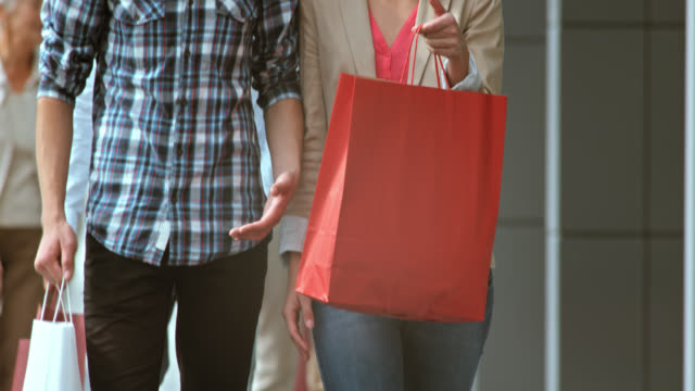 SLO MO young couple walking with shopping bags video