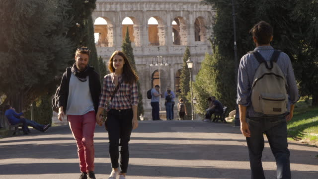 Young couple walks in park road holding hands when attractive man glances at girlfriend. She gets distracted and boyfriend gets jealous. Disoloyal girl and envy. Colosseum in the background in rome at sunset. Slow Motion video