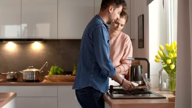 genç çift birlikte bulaşık yıkama - ev temizleme stok videoları ve detay görüntü çekimi