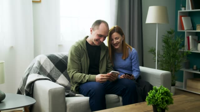 A young couple watching a fun video on a smartphone in their cozy living room video