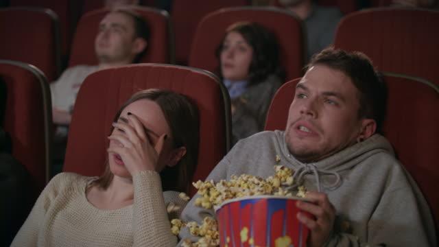 stockvideo's en b-roll-footage met jong koppel kijken naar horrorfilm in de bioscoop. guy strooi popcorn - popcorn