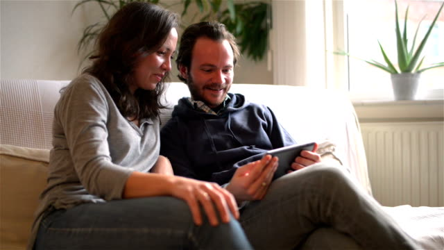 DOLLY: Young couple watching TV on tablet computer video