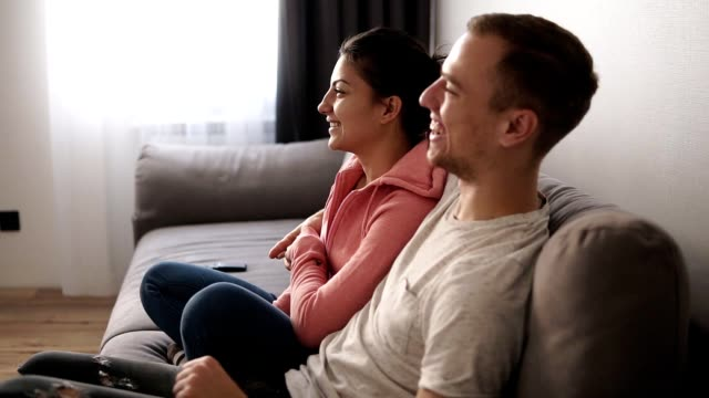 Young couple watching TV on the grey sofa at home in bright living room. Exciting couple interested on tv show. Side view