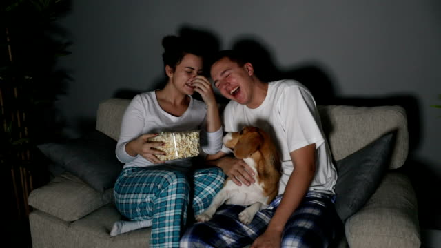 young couple watching tv together - pajamas stock videos & royalty-free footage