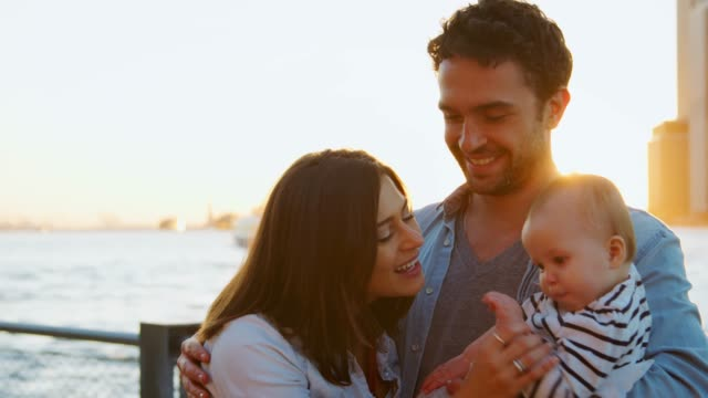 young couple with baby standing at riverside in manhattan - tre persone video stock e b–roll