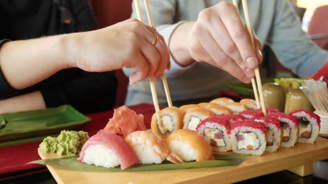 Young couple with chopsticks takes sushi from a plate in a japanese restaurant. video