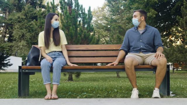 stockvideo's en b-roll-footage met slo mo jong paar met beschermende gezichtsmaskers die handen uitspreiden terwijl het zitten op de bank in openbaar park - daten