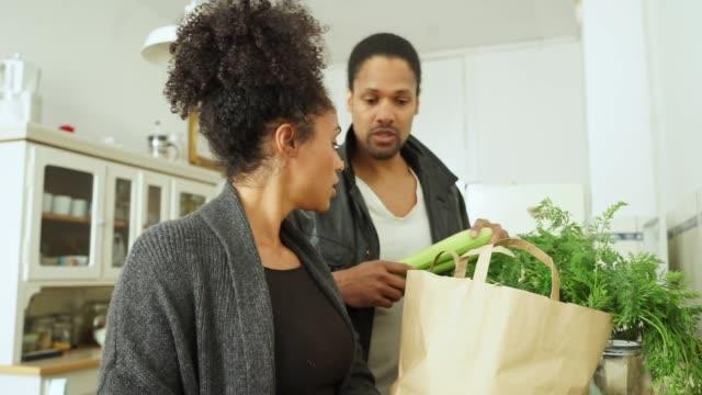 キッチンでのショッピングに若いカップルします。 - 荷物をとく点の映像素材/bロール