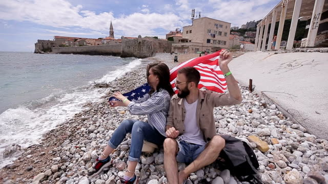 Young couple with USA flag on beach