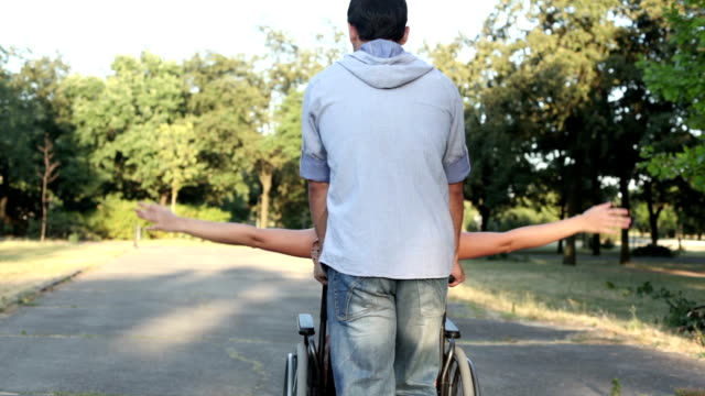 HD: Young Couple with wheelchair walking in a park. Young Couple, man and woman in a wheelchair, walking in a park. Rear view, they are moving forward and leaving the scene. pushing wheelchair stock videos & royalty-free footage
