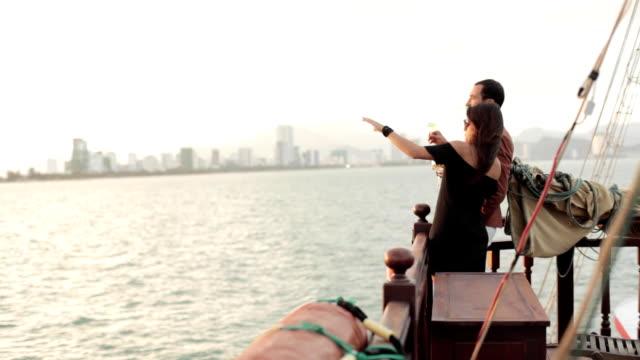 若いカップル ワインとメガネを楽しむクルーズ船の甲板に沈む夕日 - デッキ点の映像素材/bロール