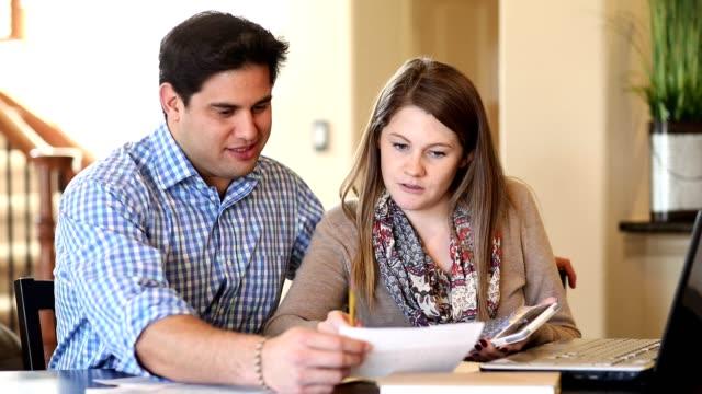 Jeunes couples travaillant sur les finances de famille ensemble à la maison. - Vidéo