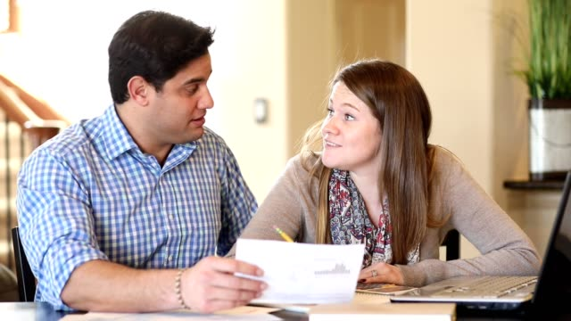 Young couple working out family finances together at home. video