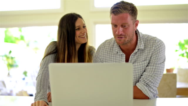 DOLLY: Young couple working with laptop video